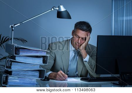 Tired Businessman Writing On Document While Working Late
