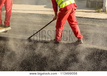Construction Worker Leveling Fresh Asphalt Pavement During Road Repair