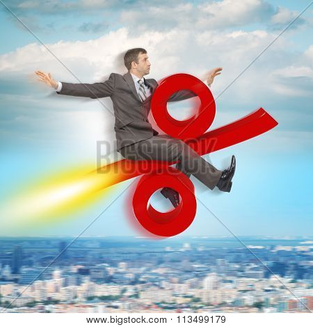 Businessman flying on percent sign