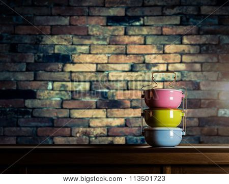 Colorful Tiffin Carrier On Wooden Cupboard With Blurred Vintage Brick Wall
