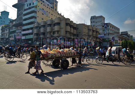 Men pushing wagon of bags in Dhaka