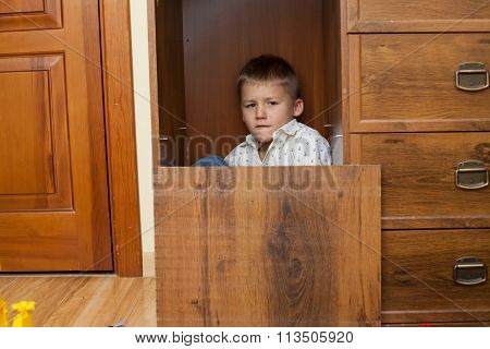 Little Boy Hiding In A Cupboard