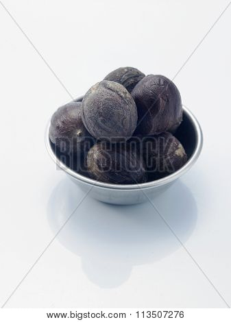 bowl of the nutmeg on the white background