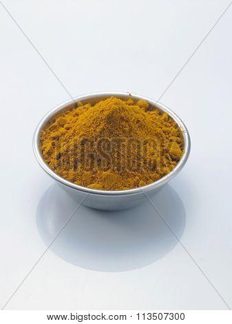 bowl of tumeric powder on the white background