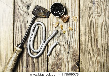 A vintage brazing copper  iron, a solid tin wire and some colophony on a wooden background