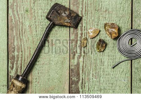A vintage brazing copper  iron, a solid tin wire and some colophony on a green wooden background