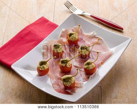 parma ham with stuffed tomatoes, traditional italian appetizer