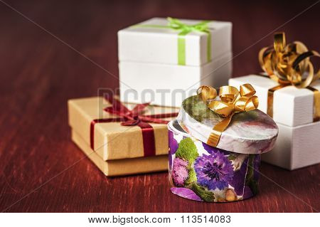 Closeup of gift boxes tied ribbons on a red wooden background