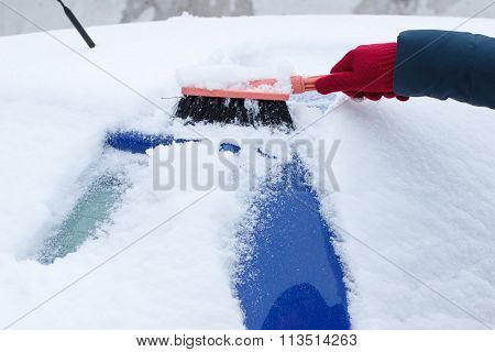 Hand Of Woman Using Brush And Remove Snow From Car And Windscreen