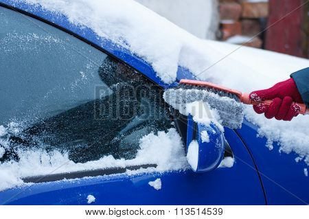 Hand Of Woman Using Brush And Remove Snow From Car, Windscreen And Mirror