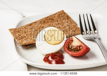 Close-up of half a boiled egg with a slice of tomato, sauce and dry rye loaves on a white plate