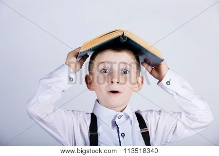 Little boy holding book on head
