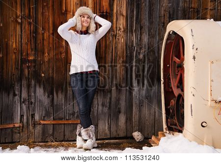 Relaxed Young Woman In Furry Hat Standing Near Rustic Wood Wall