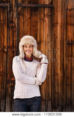 Woman In White Knitted Sweater And Furry Hat Near Wood Wall
