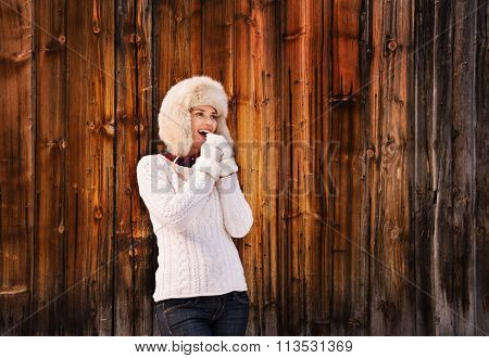 Smiling Woman Blowing Warm Breath On Her Hands Near Wood Wall