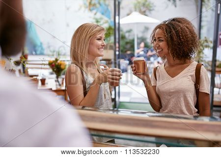 Friends Having A Cup Of Coffee At Cafe