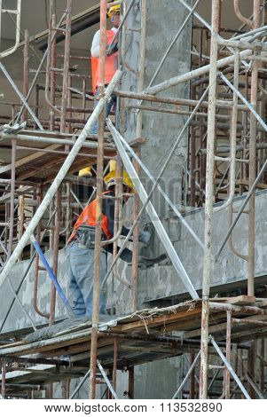 Group of construction workers plastering building wall