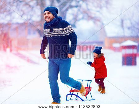 Happy Father And Son Having Fun With Sledge Under Winter Snow