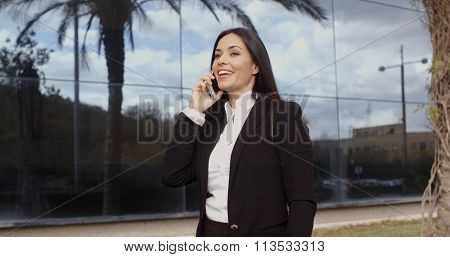 Laughing vivacious woman talking on a mobile