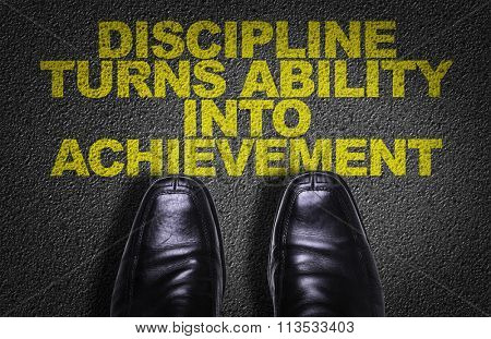 Top View of Business Shoes on the floor with the text: Discipline Turns Ability Into Achievement