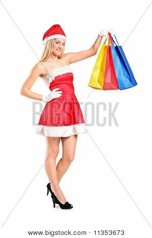 Full Length Portrait Of A Woman Dressed As Santa With Shopping Bags