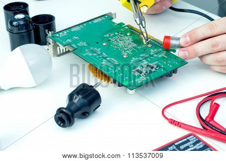 Electrician using a soldering iron in a workshop