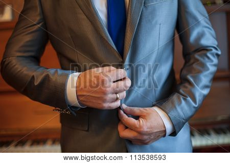 man buttoning his jacket, with a wedding ring on his hand
