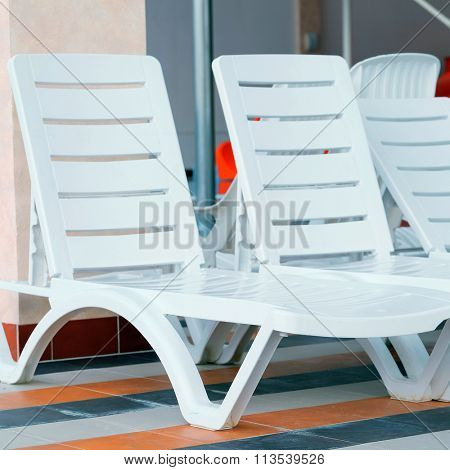 swimming pool and many white empty chaise-longue