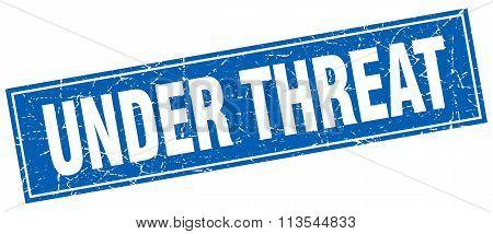 Under Threat Blue Square Grunge Stamp On White