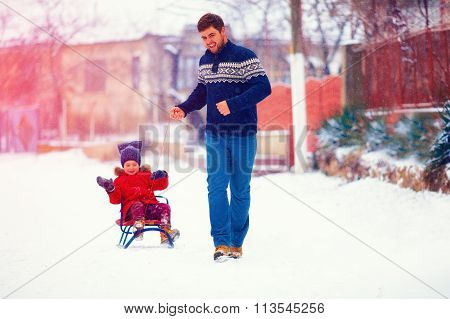 Happy Family Riding The Sledge Under Winter Snow, On Village Street