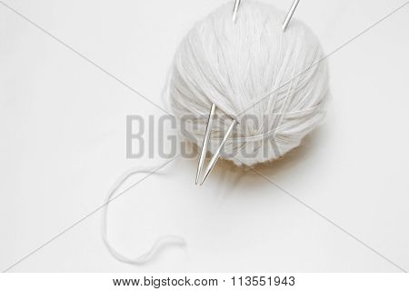 Ball Of White Wool Yarn With Knitting Needles On White Background