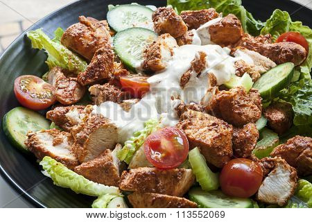 Tandoori chicken salad on black plate.