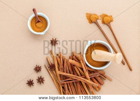 Composition Of Cinnamon Stick And Cinnamon Powder In White Mortar With Star Anise And Wooden Spoon O