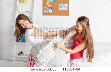 happy teen girl friends fighting pillows at home