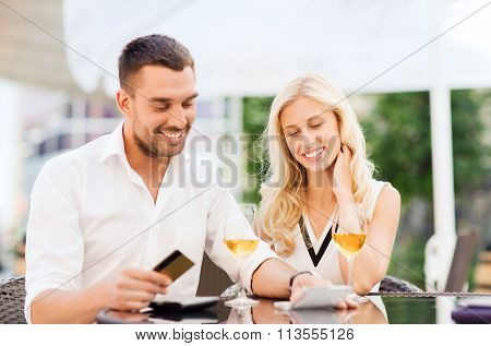 happy couple with bank card and bill at restaurant
