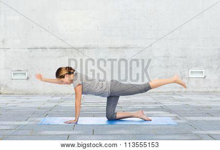 woman making yoga in balancing table pose on mat