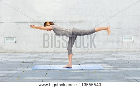 woman making yoga warrior pose on mat outdoors