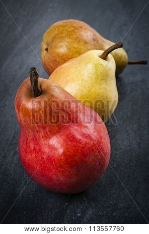 Three bright ripe bartlett pears on dark grey background