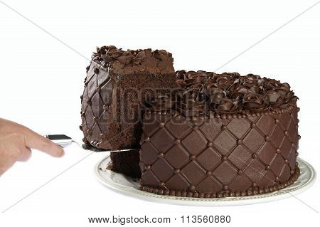 Hand with server removing large slice triple chocolate rose cake isolated on white