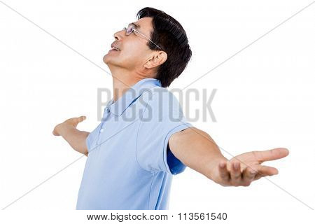 Man with arms outstretched looking up while standing against white background