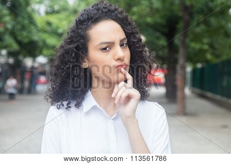 Thinking Caribbean Woman With Curly Hair In A Park