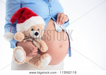 Mom Expecting Baby. Pregnant Woman Holding Blue Baby Socks And Fluffy Bear In Her Hands Isolated On