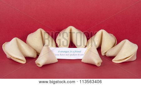 Chinese Fortune Cookies on a red background one broken open with fortune showing