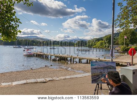 Artist Painting The Lake And A Pier In Ambleside In Lake Windremere, Cumbria