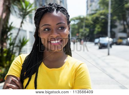 African American Woman In A Yellow Shirt In City Looking Sideways