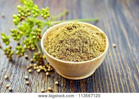 Coriander powder in bowl on board
