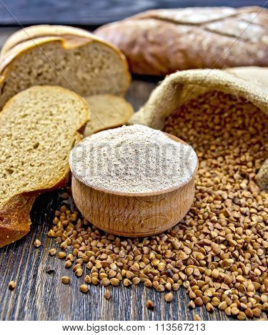 Flour buckwheat in bowl with cereals and breads on board