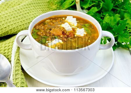 Soup lentil with spinach and cheese on board