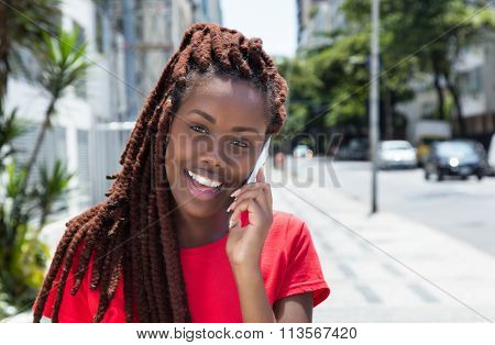 African Woman With Dreadlocks Speaking At Phone In The City