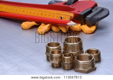 Parts of plumbing fitting with wrench and tools